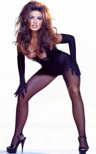 Carmen Electra looking hot in corset and fishnets. Looks like a young Raquel Welch with very long legs and heels.