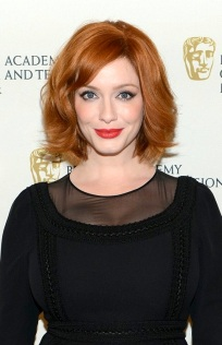 Sexy redhead Christina Hendricks wears black top that struggles to contain her large cleavage