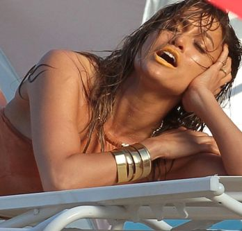 Jennifer Lopez open mouth in nude swimsuit. With orange lipstick and gold jewelery