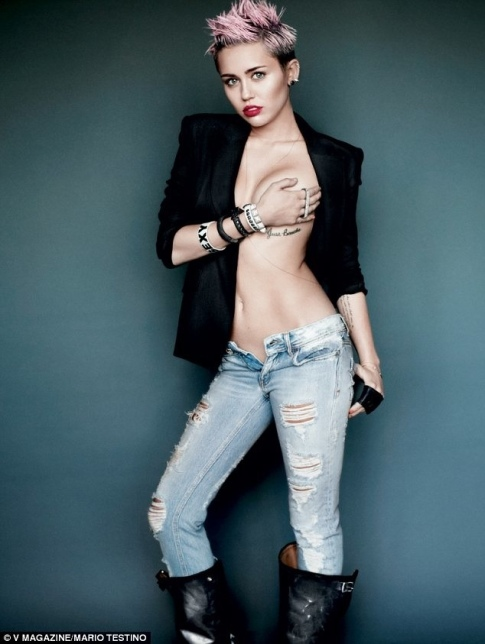Miley Cyrus holding her breast. Singer naked under open jacket.