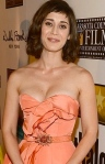 Lizzy Caplan shows cleavage in peach gown. Mean Girls star, Janis Ian