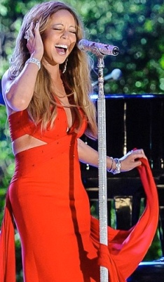 Mariah Carey in red dress with cleavage showing plunge neckline and nude side panels. Macy's Fourth of July Fireworks Spectacular