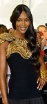 Naomi Campbell in black dress with gold breast plate feature