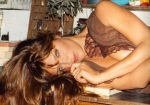 Supermodel Helena Christensen shows breasts while lying down