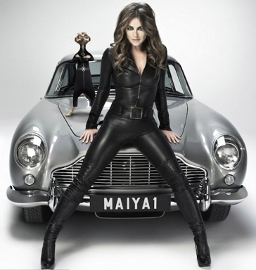Liz Hurley legs astride Aston Martin DB5 in leather catsuit. With Maiya the meerkat spy.