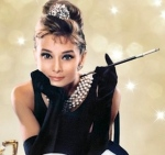 Audrey Hepburn as Holly Golightly in Breakfast at Tiffanys wearing little black dress, black gloves and with cigarette holder.