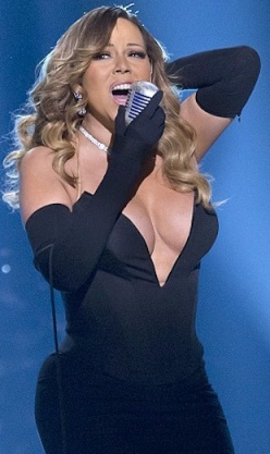 Mariah Carey shows extreme cleavage in black dress held together with tit tape to avoid wardrobe malfunction