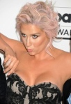 Kesha pushes her boobs back into dress to avoid wardrobe malfunction